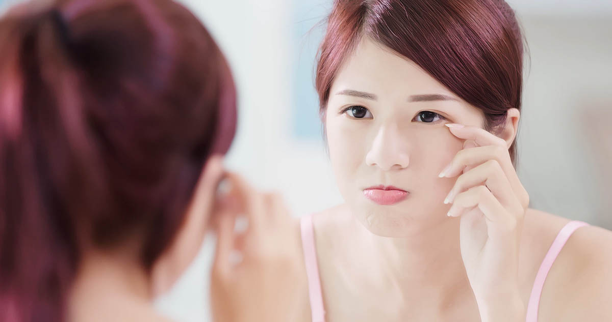 Woman look mirror and touch her eyes